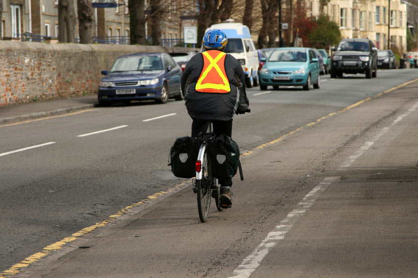 A photo of a cyclist wearing a reflective vest and helmet as he goes down a bike lane.